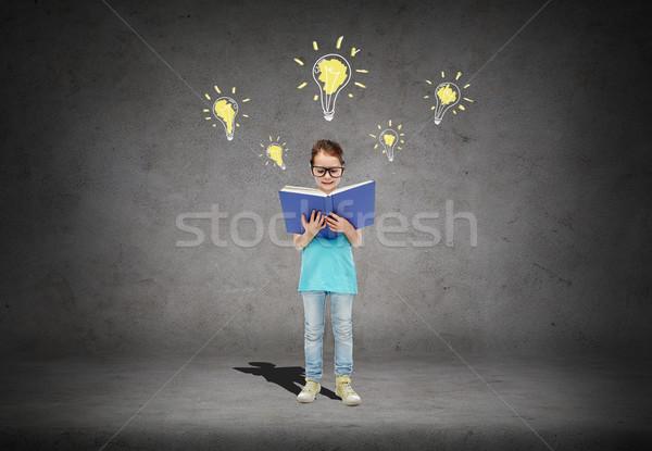 Boldog kislány szemüveg olvas könyv gyermekkor Stock fotó © dolgachov