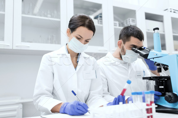 scientists with clipboard and microscope in lab Stock photo © dolgachov