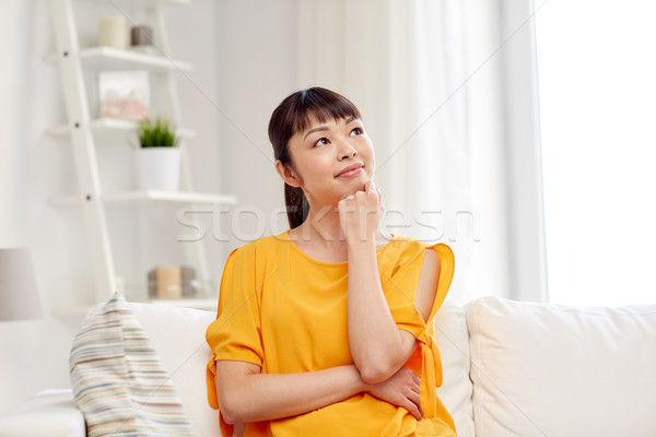happy asian young dreaming woman at home Stock photo © dolgachov
