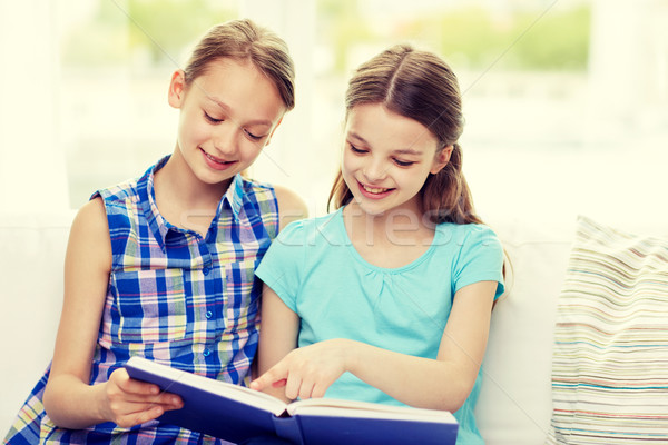 two happy girls reading book at home Stock photo © dolgachov