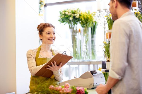 florist woman and man making order at flower shop Stock photo © dolgachov
