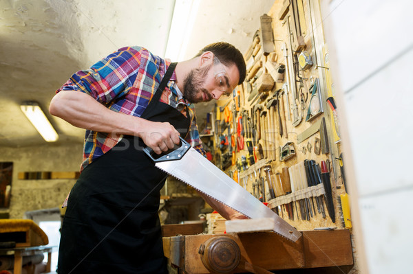 carpenter working with saw and wood at workshop Stock photo © dolgachov