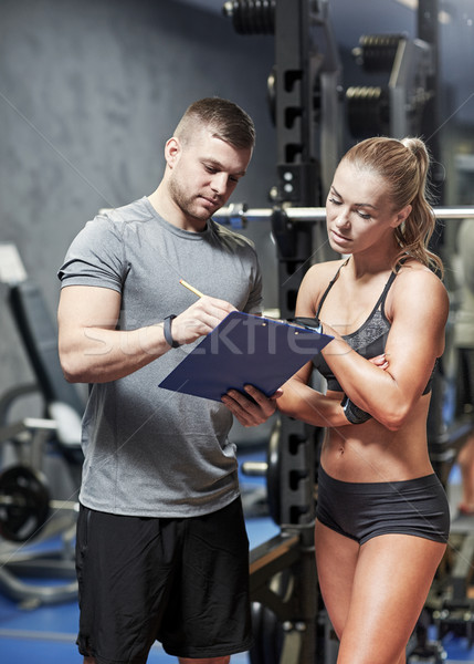 young woman with personal trainer in gym Stock photo © dolgachov