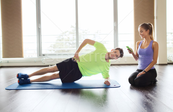 man and woman doing plank exercise on mat in gym Stock photo © dolgachov