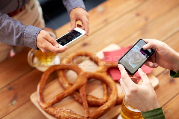 Mains bretzel smartphone personnes alimentaire Photo stock © dolgachov