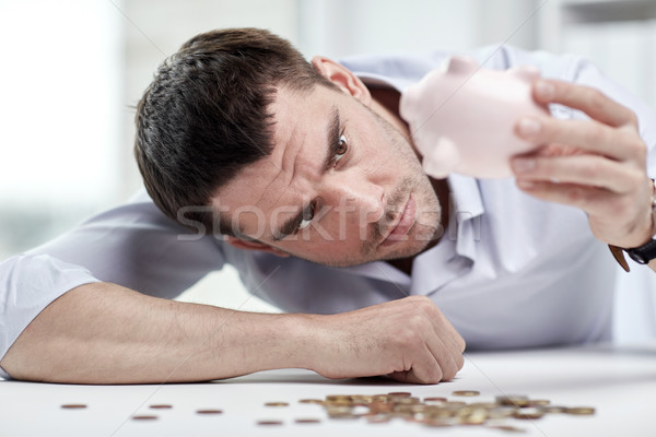 businessman with piggy bank and coins at office Stock photo © dolgachov
