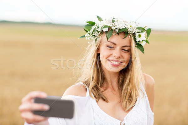 Stock photo: happy young woman taking selfie by smartphone
