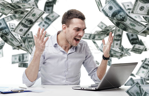 angry businessman with laptop and falling money Stock photo © dolgachov