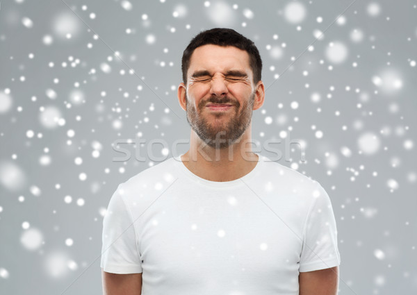 man screwing up his face over snow background Stock photo © dolgachov