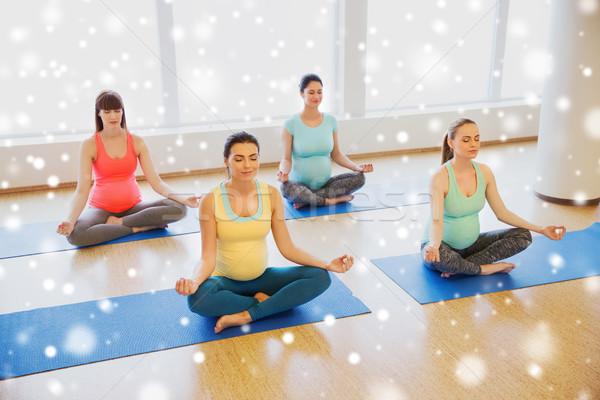 happy pregnant women exercising yoga in gym Stock photo © dolgachov
