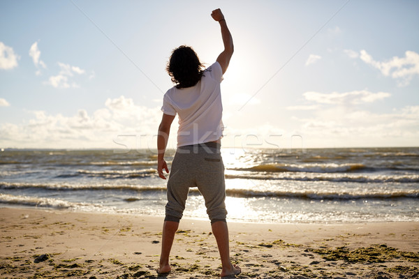 man with rised fist on beach Stock photo © dolgachov