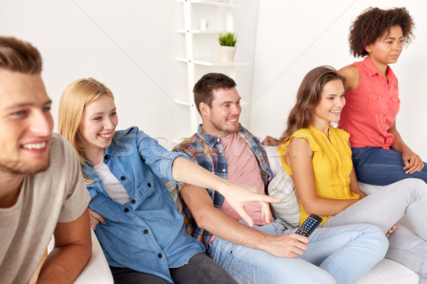 happy friends with remote watching tv at home Stock photo © dolgachov