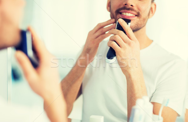 close up of man shaving beard with trimmer Stock photo © dolgachov