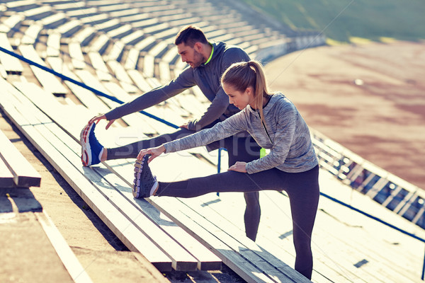 Stock photo: couple stretching leg on stands of stadium
