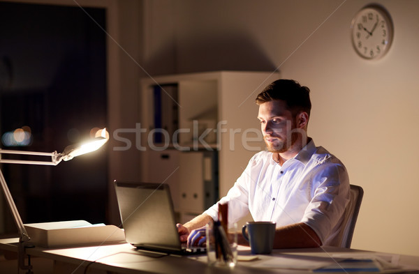 businessman typing on laptop at night office Stock photo © dolgachov