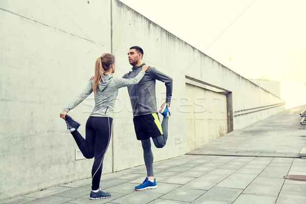 couple of sportsmen stretching leg on city street Stock photo © dolgachov