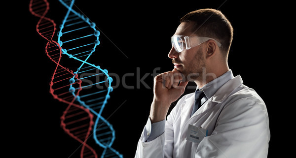 scientist in goggles looking at dna molecule Stock photo © dolgachov