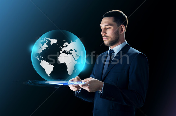 businessman with tablet pc and earth projection Stock photo © dolgachov