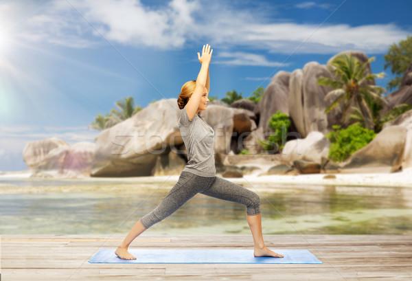 Heureux femme yoga guerrier posent plage Photo stock © dolgachov