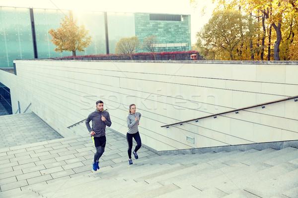 happy couple running upstairs on city stairs Stock photo © dolgachov