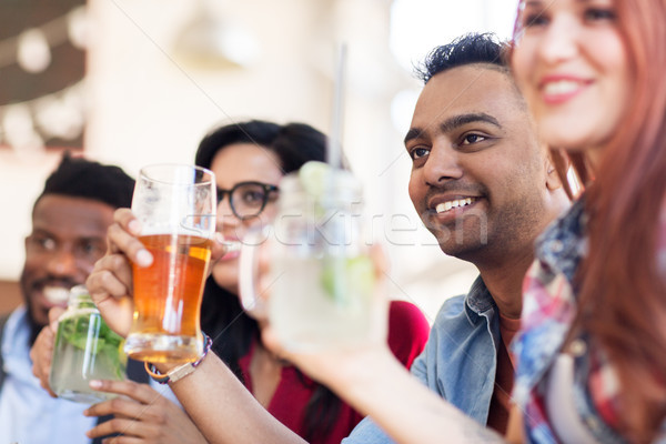 Stock photo: happy friends with drinks at restaurant