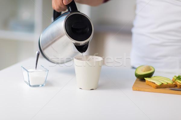 Férfi bogrács készít tea reggeli otthon Stock fotó © dolgachov