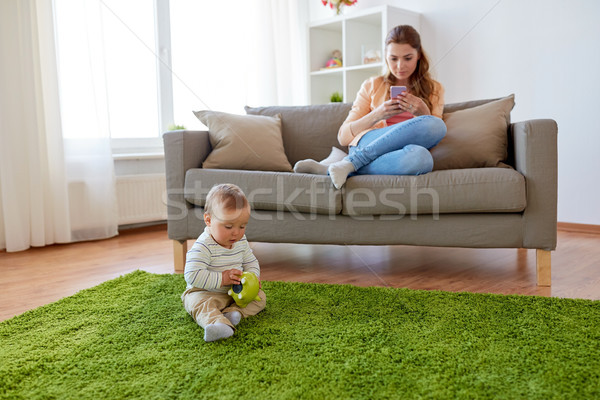 Stock photo: mother with smartphone and baby playing at home