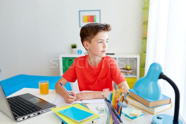 student boy with laptop writing to notebook Stock photo © dolgachov