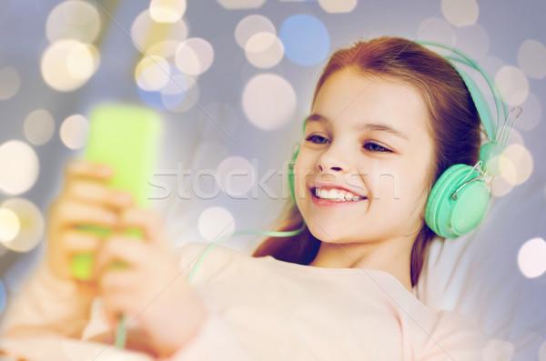 girl in headphones with smartphone over lights Stock photo © dolgachov