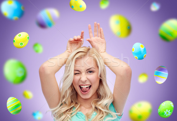 happy woman making bunny ears over easter eggs Stock photo © dolgachov