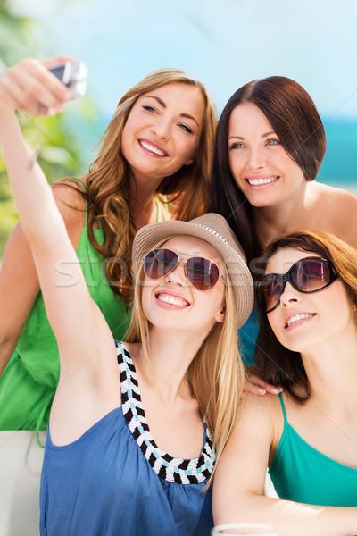 girls taking photo in cafe on the beach Stock photo © dolgachov
