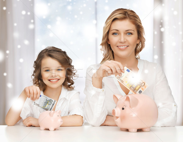 mother and daughter with piggy banks and money Stock photo © dolgachov