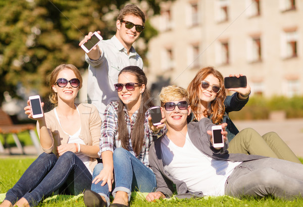 students showing smartphones Stock photo © dolgachov