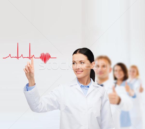 smiling female doctor pointing to cardiogram Stock photo © dolgachov