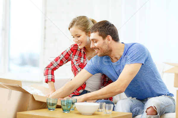 smiling couple unpacking kitchenwear Stock photo © dolgachov