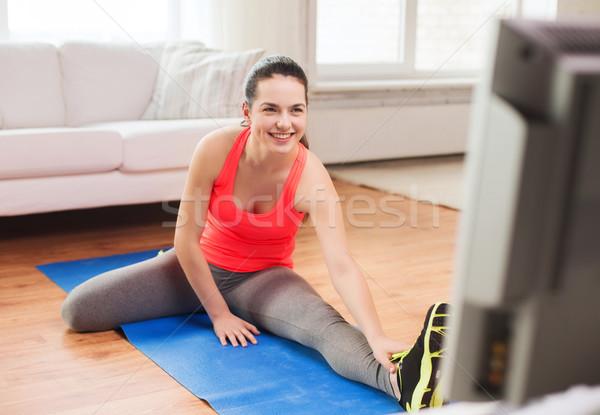 smiling teenage girl streching on floor at home Stock photo © dolgachov