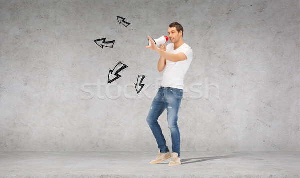 handsome man with megaphone over concrete wall Stock photo © dolgachov