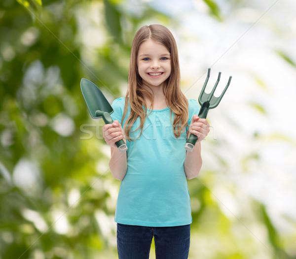Sorridente little girl ancinho escavar jardim pessoas Foto stock © dolgachov