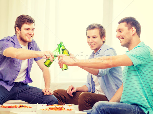 smiling friends with beer and pizza hanging out Stock photo © dolgachov
