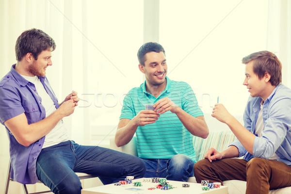 happy three male friends playing poker at home Stock photo © dolgachov