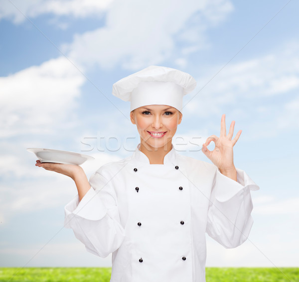 smiling female chef with plate showing ok sign Stock photo © dolgachov