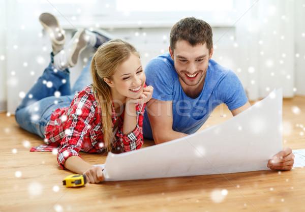 smiling couple with  blueprint at home Stock photo © dolgachov