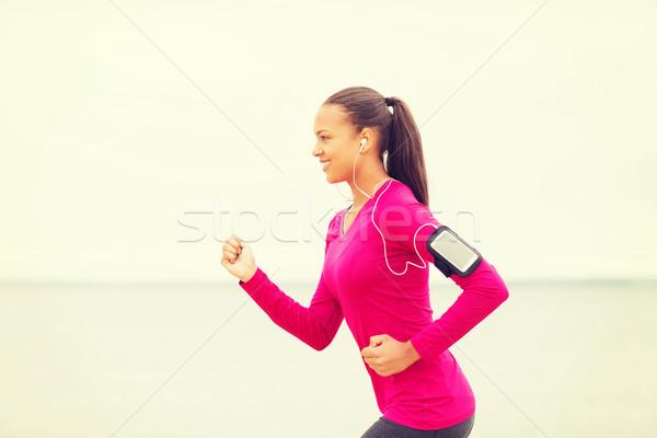 Glimlachend jonge vrouw lopen buitenshuis sport fitness Stockfoto © dolgachov
