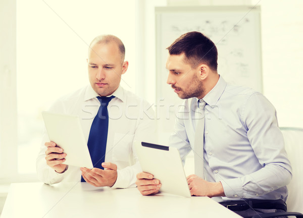 two serious businessmen with tablet pc in office Stock photo © dolgachov