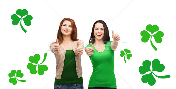 two smiling girls showing thumbs up with shamrock Stock photo © dolgachov