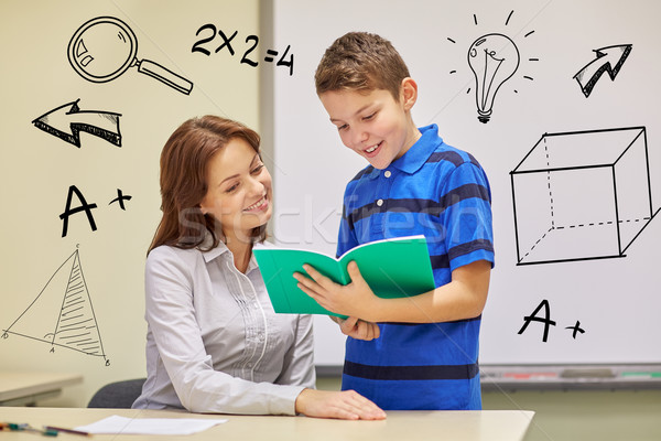 school boy with notebook and teacher in classroom Stock photo © dolgachov