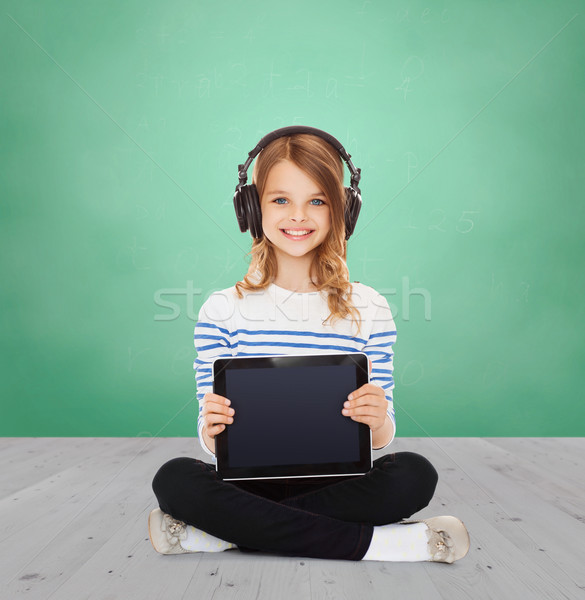 happy girl with headphones showing tablet pc Stock photo © dolgachov