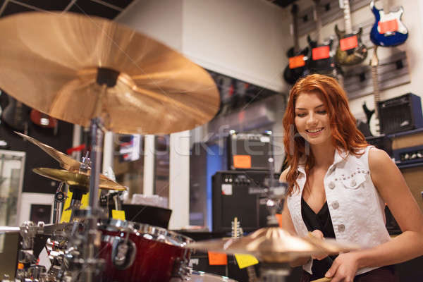 smiling musician playing cymbals at music store Stock photo © dolgachov