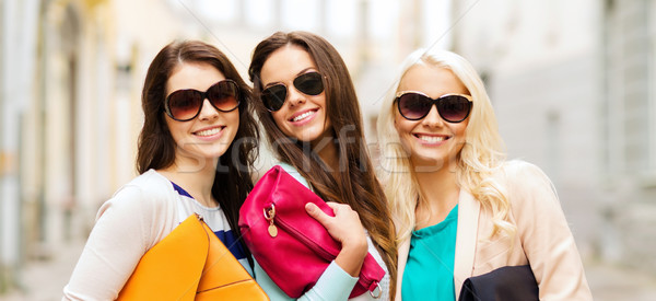 three smiling women with bags in the city Stock photo © dolgachov