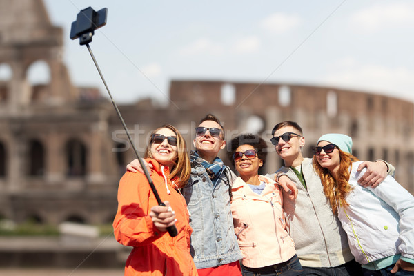 happy friends with smartphone selfie stick Stock photo © dolgachov